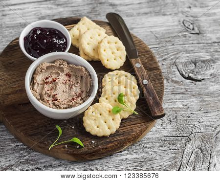 Homemade chicken liver pate cranberry sauce and homemade cheese biscuits. Delicious snack or appetizer with wine. On light wooden rustic background