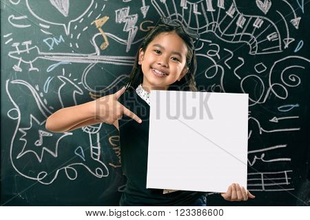 Portrait of cute girl in eyeglasses looking at camera by the blackboard with chalk drawings of musical instruments.