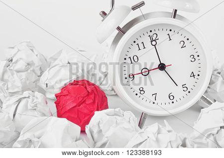 White alarm clock in the balls of crumpled white paper with a red ball of crumpled paper on a white background