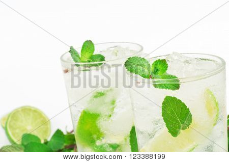 closeup two mojito cocktail with lime and mint in tumbler glass on white background