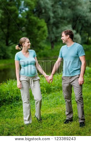 Adorable young pregnant woman and happy handsome man smiling, holding each other hands and looking at each other in summer park. Happy family and pregnancy concept. Mother's Day