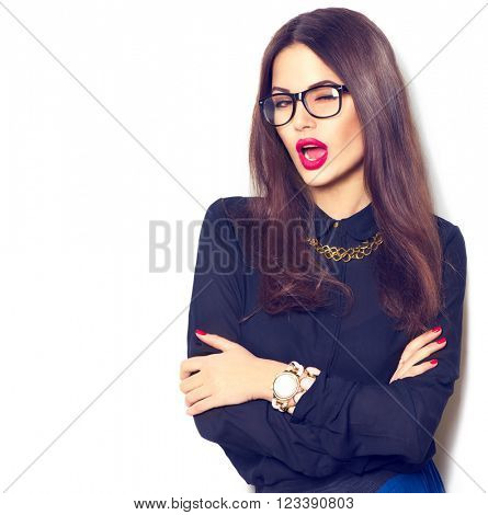 Beauty sexy winking fashion model girl wearing glasses, isolated on white background. Beautiful young brunette woman with trendy accessories posing in studio