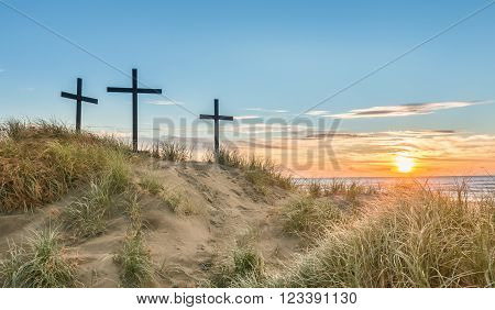Three crosses on a sand dune with a sunset over the sea.