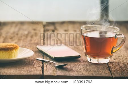 hot tea cup with butter cake and smartpho on the table on the winter day, vintage toning