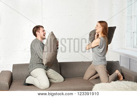 Couple fighting together with pillows on couch ** Note: Soft Focus at 100%, best at smaller sizes