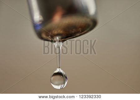 Water drop about to fall from a leaking faucet