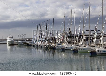 SOCHI, RUSSIA - November 06, 2015: The mooring with catamarans and boats against an emblem of the Olympic Games and the gray sky. Sochi, Russia