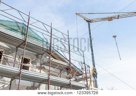 Construction scaffolding of a building under renovation and a crane.