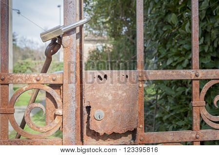 Rusty metal gate closed with padlock - concept image
