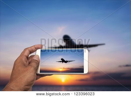 Hand with smart phone shooting photograph on blurred airplane and beach sunset in twilight