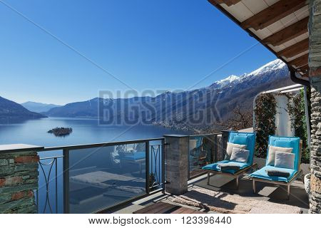 Terrace of house with comfortable sun beds and lake view