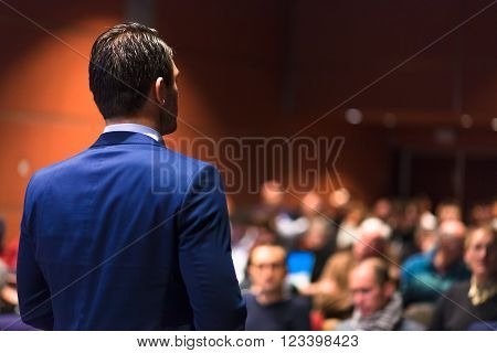 Speaker giving a talk on corporate Business Conference. Audience at the conference hall. Business and Entrepreneurship event.