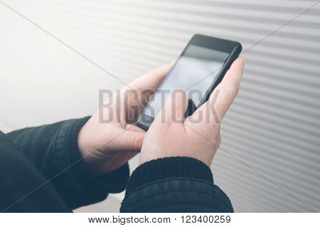 Woman using smartphone on the street facing the wall while holding mobile phone young adult female in urban surrounding texting sms or reading message retro toned image selective focus.