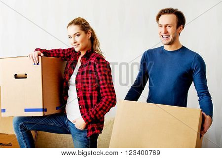 Happy couple carrying cardboard boxes in new home