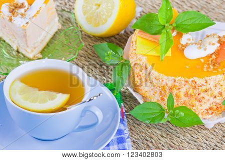 a delicious sweet cake is beautifully decorated and cup of tea with a lemon