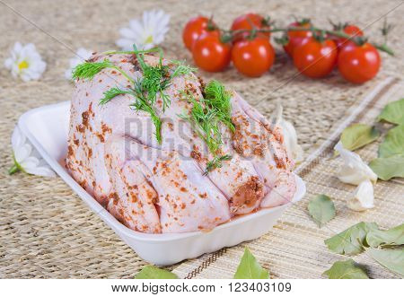 chicken carcass with seasoning and tomatoes with fresh greenery