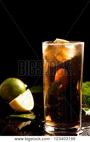 glass of cola or coke with ice cubes, lemon slice and mint