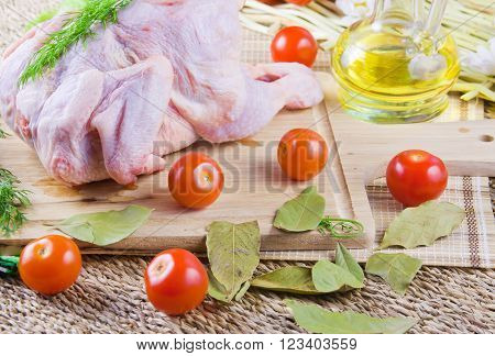 chicken carcass on a wooden board with tomatoes and fresh greenery