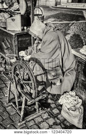 Elderly woman uses the cocoons of silkworms to spin using an old spinning wheel of wood.