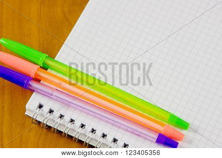school belonging notebook and three pens lays on a table