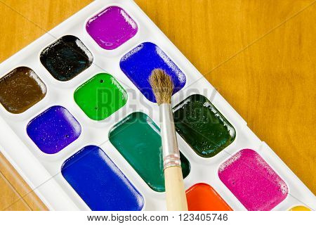 Bright school accessories, water colour paints and brush