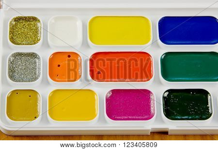 Bright school accessories, water colour paints close up