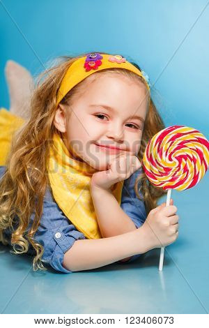 Funny little girl with long, curly hair,with a yellow handkerchief around his neck, a sweet smile,is dressed in a blue shirt and yellow pants,posing in Studio laying on the floor on a blue background holding a large,round, colourful Lollipop