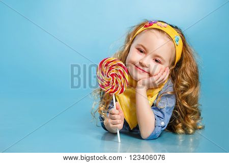 Funny little girl with long, curly hair,with a yellow handkerchief around her neck, a sweet smile,is dressed in a blue shirt and yellow pants,posing in Studio laying on the floor on a blue background holding a large,round, colourful Lollipop