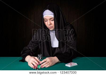 Nun rakes to their poker chips sitting at green poker table