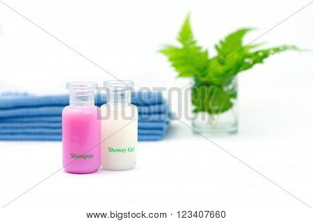 Shampoo and Shower gel on white background. Shampoo Shower gel with blurred blue cloth and green leaves in a glass of water.