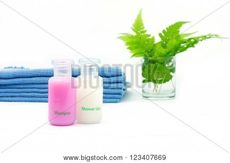 Shampoo and Shower gel on white background. Shampoo Shower gel with blue cloth and green leaves in a glass of water.