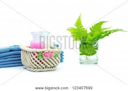 Shampoo and Shower gel put in ceramic basket on white background. Shampoo, Shower gel bottles with blue cloth and green leaves in a glass of water.