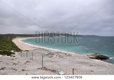 Elevated view of the secluded Foul Bay Beach from White Cliff Point with the turquoise Indian Ocean waters in Hamelin Bay under dark, stormy skies in Western Australia.