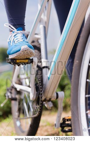 Foot on bicycle pedal, close up,  vertical image