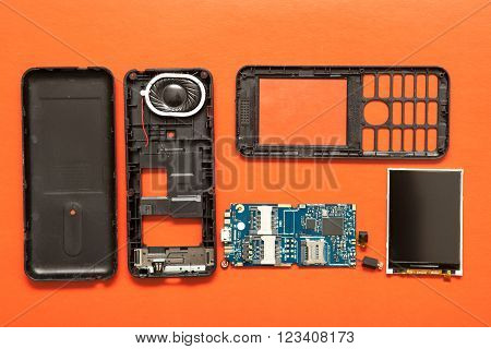 Disassembled Button Phone On A Red Background. Details Top View
