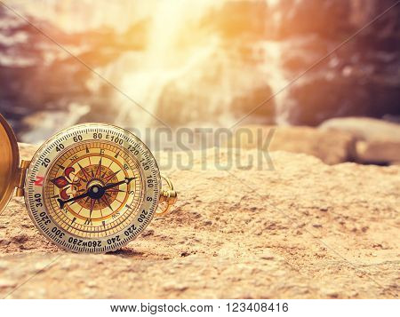 The retro compass on the rock with waterfall blurred background and sunlight. Vintage style and filtered process