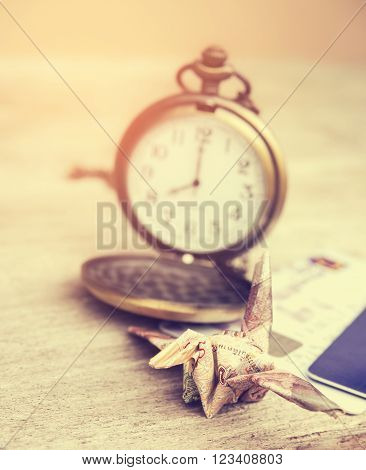 Financial time concept. Origami crane or bird made from a money note with watch time in out of focus background. Vintage style and filtered process.