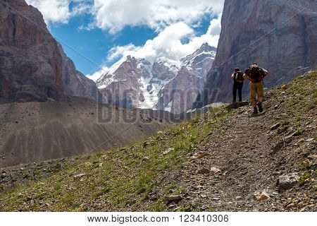 People with Backpacks Walking Up on Rocky Trail along Green Meadow and High Rock Walls and Summits on Background Blue Sky Clouds Sunny