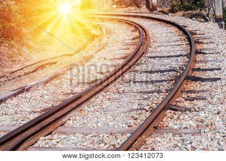 Railway curve in forest at sunset time.