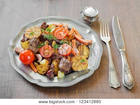 Roast venison meat with vegetables on a vintage pewter plates and old cutlery on a wooden table