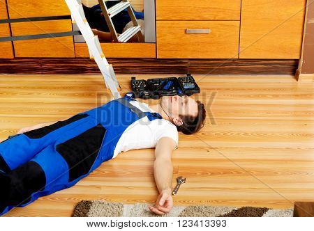 Young handyman fell from a ladder and lies on the floor