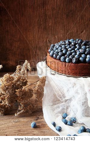 Chocolate cake with icing blueberries. Chocolate cake with chocolate frosting and blueberries on a black stand on dark background. chocolate pie and berries