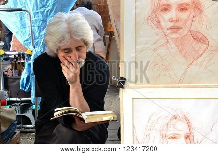 PARIS / FRANCE - September 24 2011: Artist read a book in Montmartre the legendary bohemian artist district of Paris. Next to the painter stands his work.