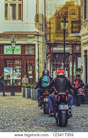 Bucharest Romania - October 6 2013: Motorcyclists ride powerful sport motorcycles on the cobblestone streets of the historic center Lipscani the Bucharest's the most attractive area for tourists.