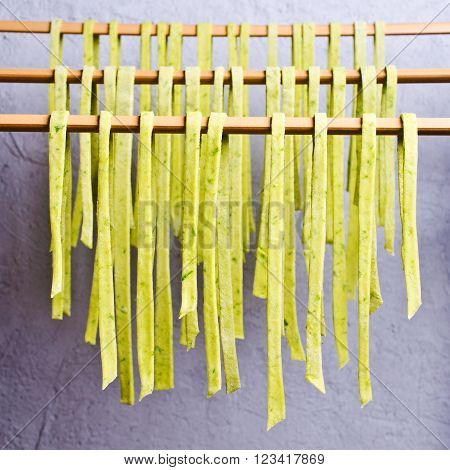 Homemade tagliatelle green hanging to dry. Selective focus.