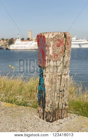 Old weathered and beautifully colored mooring pole in the harbor of West-Terschelling in the North of the Netherlands