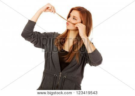 Teenage woman making moustache from hair