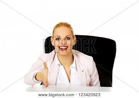Smile business woman sitting behind the desk with an open hand ready for handshake