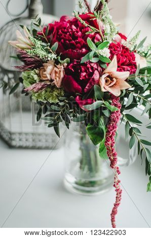 Wedding bouquet . The bride's bouquet. Bouquet of red and beige flowers greenery with a ribbon of color Marsala in vase on a white background
