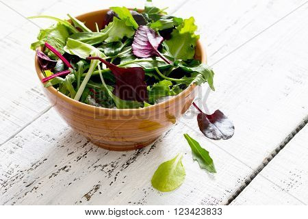 Fresh Green Mixed Salad In A Bowl On A White Wooden Table